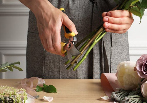 A male pair of hands carefully trims the stems of a flower grouping