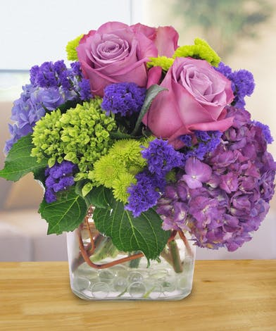 Purple roses, hydrangea and green button mums in a glass cube vase.