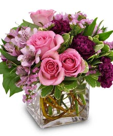 Pink roses and Peruvian lilies in a clear glass vase.