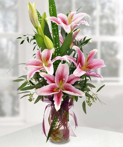 Pink stargazer lilies and greenery in a clear glass vase tied with red ribbon.