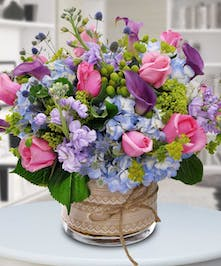 Roses, stock, calla lilies and more in a glass vase tied with ribbon.