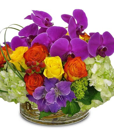 Roses, hydrangea and orchids in a variety of colors in a clear glass cylinder vase.
