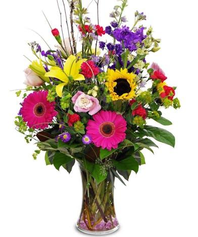 Seasonal flowers arranged in a clear glass vase.