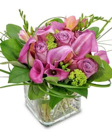 Freesia, mini callas and roses in a clear glass cube vase.