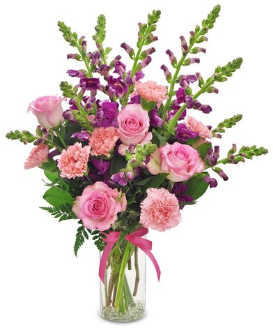 Snapdragons, carnations and roses in a clear glass vase tied with purple ribbon.