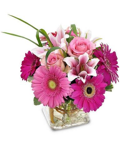 Pink stargazer lilies, gerbera daisies and other flowers in a clear glass cube vase.