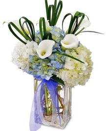 White and blue flowers in a clear glass vase tied with blue ribbon.