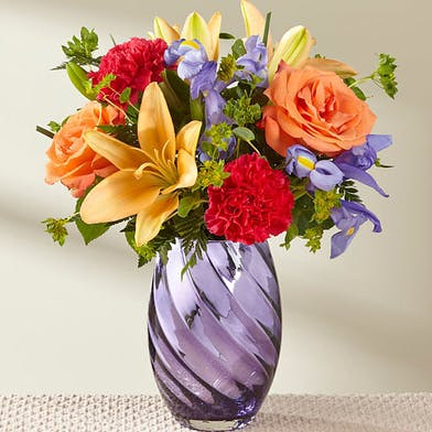 Orange, yellow, red and purple flowers in a purple glass vase.