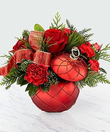 Christmas arrangement of red flowers and winter greenery in a red ornament vase