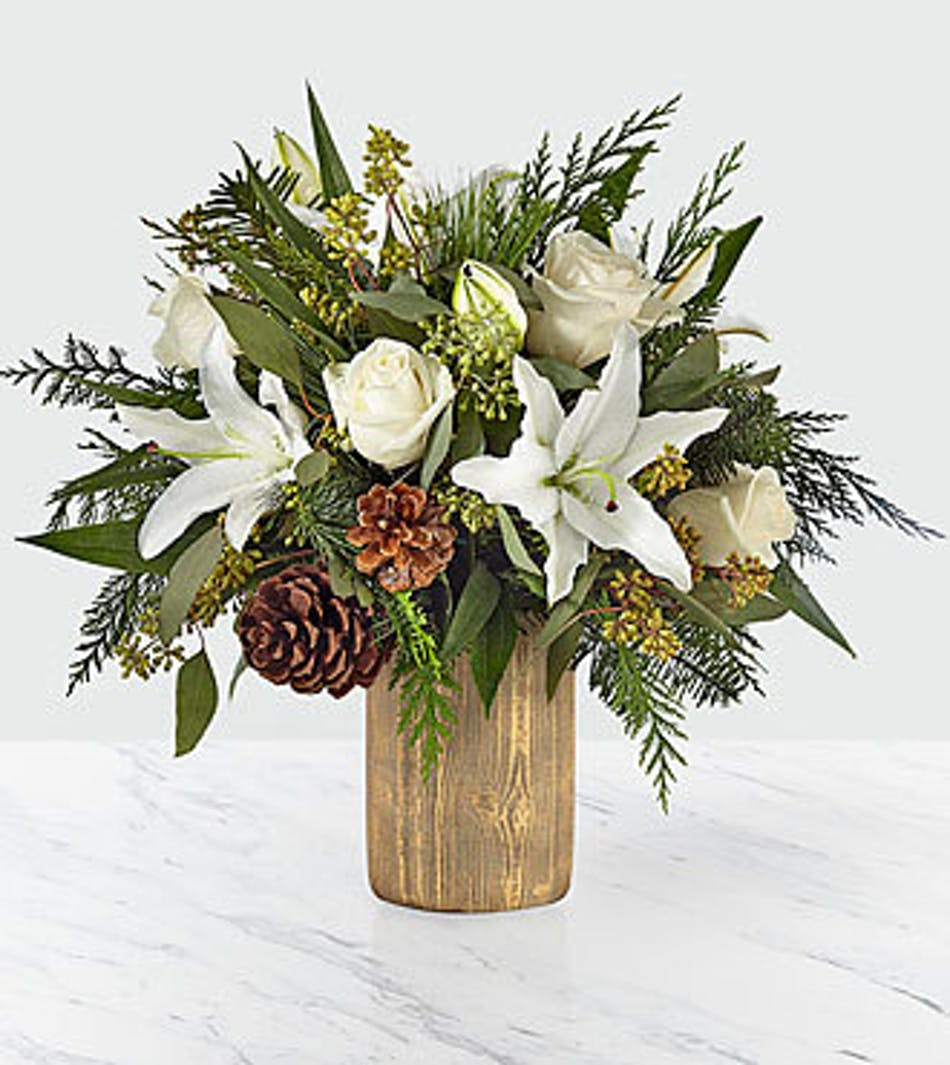 Cylinder vase of white lilies and roses, pine cones and winter greenery