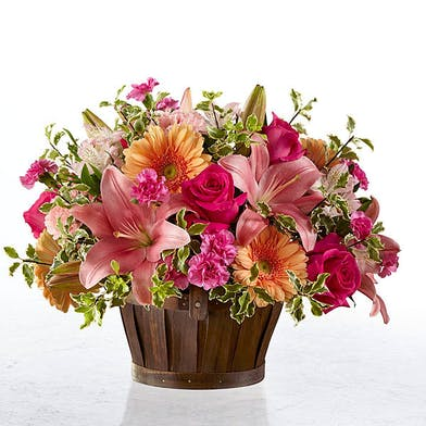 Flowers in shades of pink and purple in a magenta glass vase.