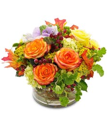 Flowers in fall colors arranged in a clear cylinder vase.