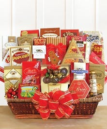 Holiday gift basket of chocolate, popcorn and other goodies tied with a bow.