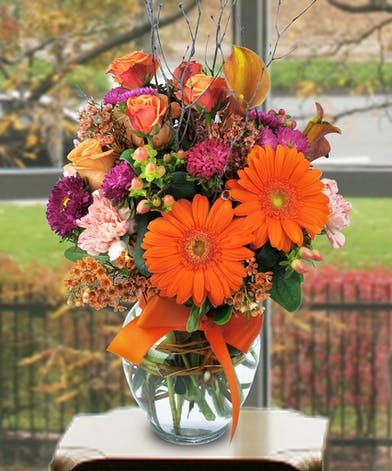 Gerbera daisies, asters, calla lilies and other flowers in a clear glass vase tied with an orange bow.