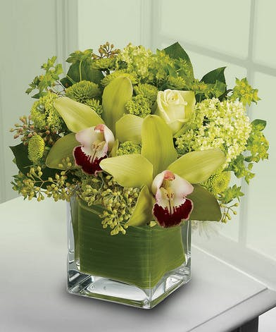 Flowers in shades of green in a green cube vase.