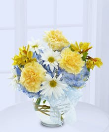 Blue, white and yellow flowers in a clear glass vase tied with a blue bow.