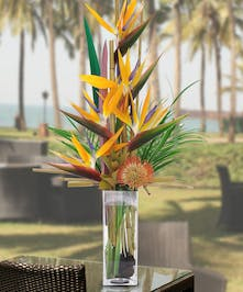 A beautiful vase filled with birds of paradise and protea.
