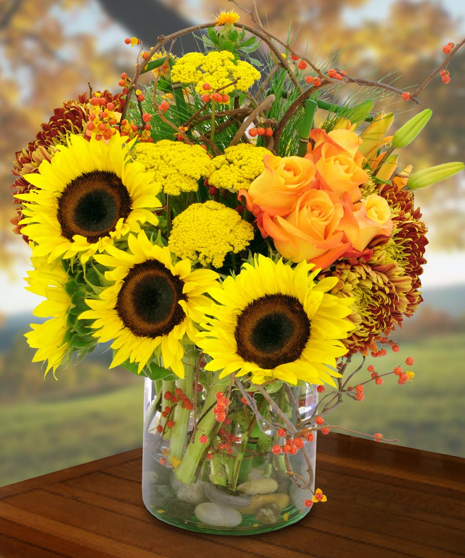 Sunflowers, roses, mums, safflowers and more in a clear glass vase.