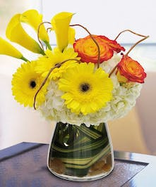 Yellow, orange and white flowers in a leaf-lined glass vase.