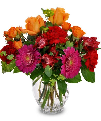Orange, yellow and red flowers in a clear glass vase.