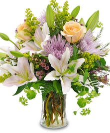 Pastel flowers in a clear glass vase.
