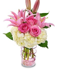 White hydrangea, lilies and pink roses in a clear glass vase.