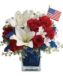 Blue glass cube vase filled with red, white and blue flowers and a miniature American flag.
