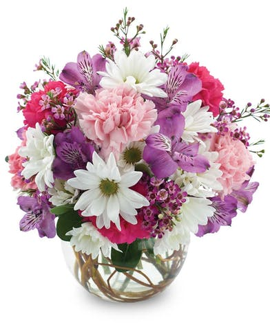 Pink, purple and white flowers in a glass bowl vase.