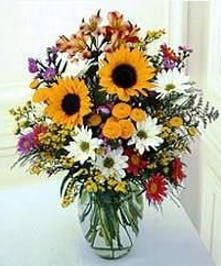 Sunflowers, delphinium and field flowers in a clear glass vase.