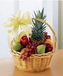 Gift basket filled with an assortment of mixed fresh fruit and  gourmet items.