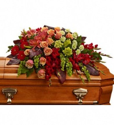 Casket spray of orange roses, lilies and more.