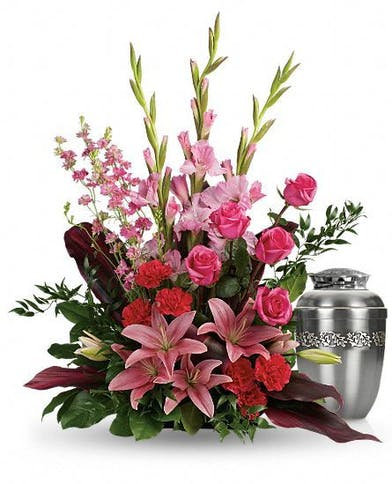 Urn arrangement of pink and red flowers for a memorial service.