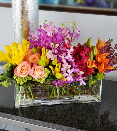 Lilies, roses and orchids in various colors inside a long glass cube vase.