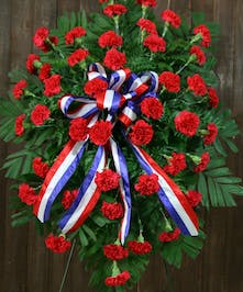 Patriotic tribute of red carnations and red, white and blue ribbon.