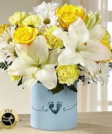 Blue vase of yellow and white flowers.