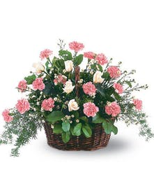 Basket filled with pink carnations in a sympathy arrangement.