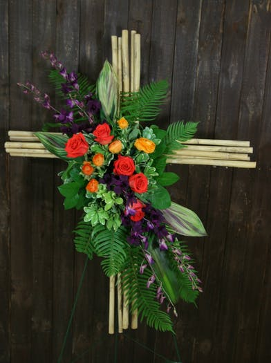 Coral roses, orange spray roses, and purple dendrobium orchids with greenery displayed on a bamboo cross.