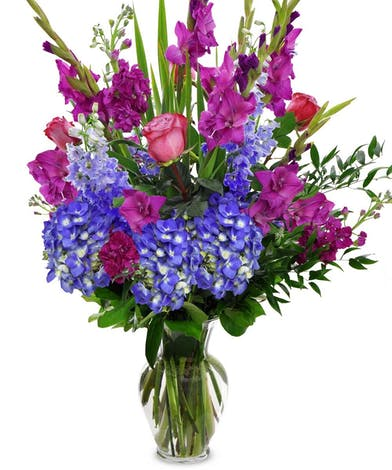 Flowers in shades of blue and purple in a clear glass vase.