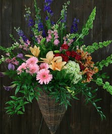 Cone-shaped basket on an easel with larkspur, lilies, gerbera daisies, calla lilies, spray roses and bells of Ireland.