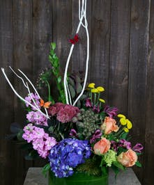 Basket of hydrangea, stock, roses, alstroemeria and more with a butterfly decoration.