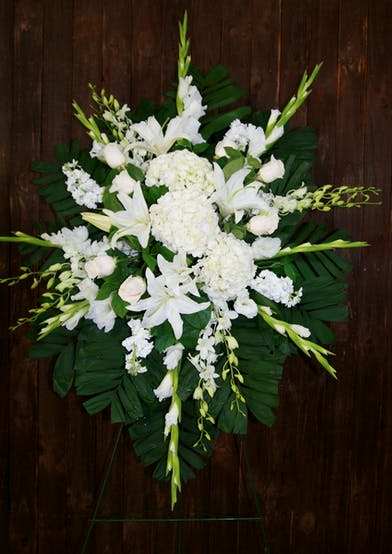 Sympathy spray of all-white flowers including hydrangea, gladiolas, dendrobium orchids and roses.