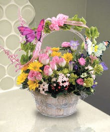 A white wicker basket filled with various pastel flowers and topped with a butterfly decoration.
