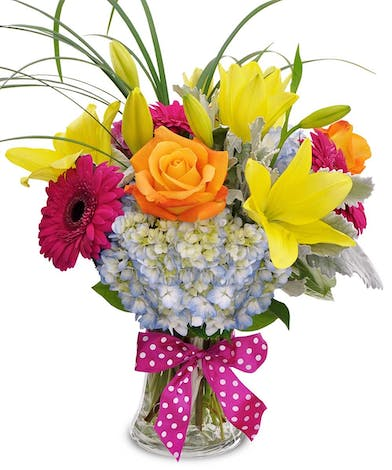 Bright orange, pink and yellow flowers in a glass vase with pink polka dot bow.