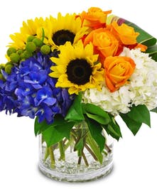 Sunflowers, orange roses, and blue hydrangea in a clear glass vase.