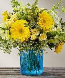 Yellow and green flowers in a blue glass vase.