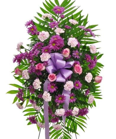 Sympathy spray of purple and lavender flowers accented with ribbon and greenery.