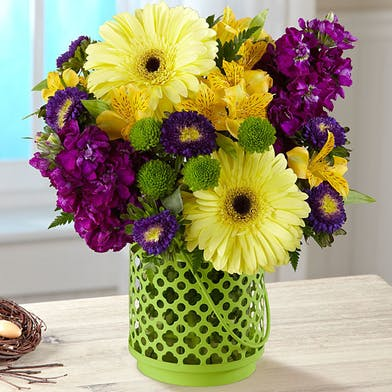 Purple and yellow flowers in a green lantern vase.