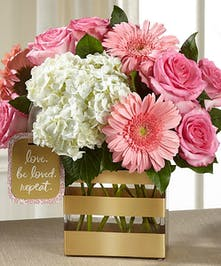 Pink and white flowers in a gold-striped cube vase.