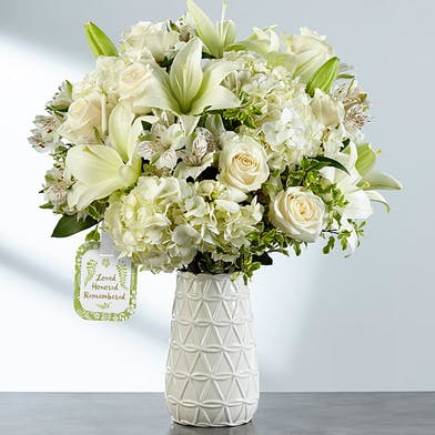 Elegant white vase filled with white roses, lilies, hydrangea and greenery.