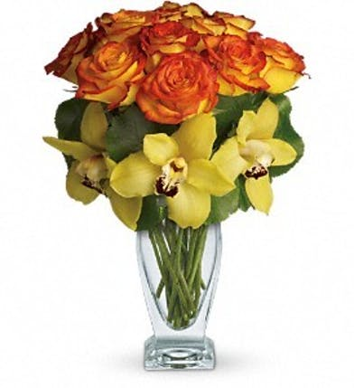 Orange roses and yellow orchids in a glass vase.